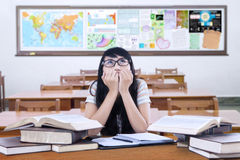 Nervous student prepares exam in the class. Picture of a female college student looks nervous while preparing for exam in the classroom with books on desk Royalty Free Stock Photo