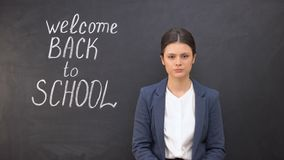 Nervous teacher looking to camera standing near board, welcome back to school. Stock footage stock footage