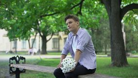 Nervous teen waiting for girlfriend with flowers, leaving bouquet, failed date. Stock footage stock video