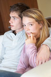 Nervous Teenage Girl Sitting On Sofa At Home. Nervous Looking Teenage Girl Sitting On Sofa At Home With Boyfriend Royalty Free Stock Images