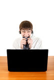 Nervous Teenager with Laptop. Nervous Young Man at the Desk with Laptop bite his Necktie Isolated on the White Royalty Free Stock Image