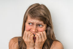 Nervous woman biting her nails royalty free stock image