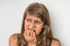 Nervous woman biting her nails. On white Royalty Free Stock Image