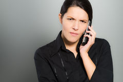 Nervous woman chatting on her mobile. Nervous beautiful young woman chatting on her mobile phone and looking at the camera with a confused expression and frown Stock Image