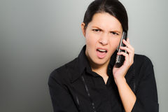 Nervous woman chatting on her mobile. Nervous beautiful young woman chatting on her mobile phone and looking at the camera with a confused expression and frown Stock Images