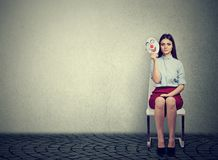 Nervous woman with clown mask before interview. Young stressed woman sitting on chair with clown mask looking nervous before interview stock images