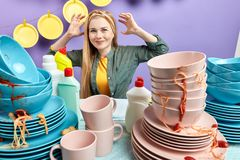 Nervous woman with raised arms standing behind dirty table stock photography