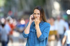 Nervous woman talking on phone on the street. Nervous woman biting nails while is talking on phone on the street royalty free stock images