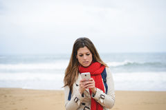 Nervous woman texting on smartphone at the beach on autumn Stock Image
