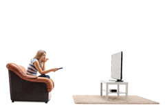 Nervous woman watching movie on TV. Nervous woman watching a movie on TV and biting her nails isolated on white background Royalty Free Stock Photography