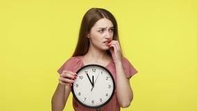 Girl holding big wall clock, biting finger nails.