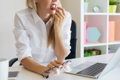 Nervous woman at work biting her nails. Nervous young business woman at work biting her nails royalty free stock images