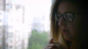 Nervous women in eyeglasses with mental disorder near window at home. Close-up stock video