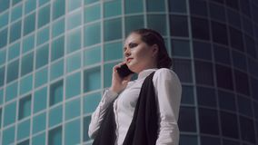 Nervous young business woman trying to make a phone call. Standing outdoors stock video footage
