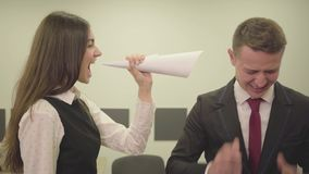 Nervous young girl in formal wear folded paper in the form of a horn and yelling at male colleague in the modern office