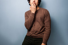 Nervous young man biting his nails Stock Images