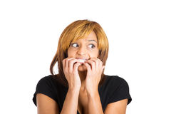 Nervous young woman biting her nails looking towards the side craving for something Stock Images