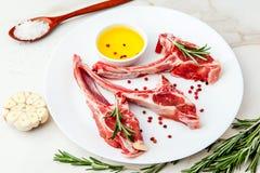 Nervures crues d'agneau avec des ingrédients pour faire cuire sur la table de marbre blanche image stock