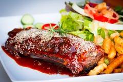 Nervures de BBQ - nervures de porc marinées avec de la salade, les pommes frites et la bavure Image libre de droits