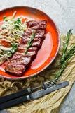 Nervures de porc américaines traditionnelles de barbecue avec une garniture de salade verte Fond gris, vue de côté images stock