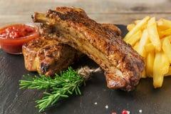 Nervures de porc cuites au four avec les pommes frites et la sauce rouge Photos stock