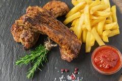 Nervures de porc cuites au four avec les pommes frites et la sauce rouge Photographie stock libre de droits