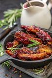 Nervures de porc cuites au four dans le lustre de miel avec de la sauce à romarin et à cerise photo libre de droits