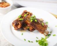 Nervures de porc frites délicieuses d'un plat, sauce, fourchette, verts photos libres de droits