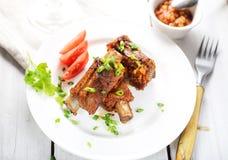 Nervures de porc frites délicieuses d'un plat, sauce, fourchette, verts images stock