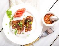 nervures de porc frites d'un plat, sauce, fourchette, verts image libre de droits