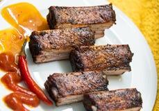 Nervures de porc fumées avec le poivron rouge sur le conseil Image libre de droits
