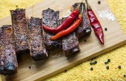 Nervures de porc grillées avec le poivron rouge sur le conseil Images stock