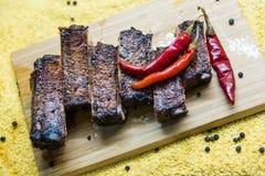 Nervures de porc grillées savoureuses avec le poivron rouge sur le conseil Photographie stock libre de droits