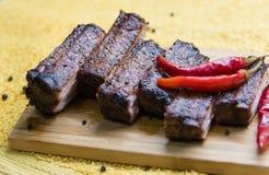 Nervures de porc savoureuses avec le poivron rouge sur le conseil Image stock