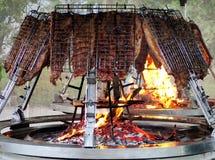 Nervures de porc sur une flamme d'un grand gril rond Images stock