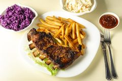 Nervures et pommes frites et salade de choux cuites au four Image stock