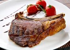Nervures grillées de viande de la plaque blanche avec des tomates Photographie stock libre de droits