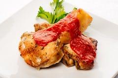 Nervures rôties de porc avec la sauce tomate du plat blanc Photos stock