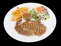 Nervurez le bifteck d'oeil servi avec des pommes frites et des salades aux légumes d'isolement sur le fond noir avec le chemin de image stock