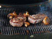 Nervurez le bifteck et les champignons de couche d'oeil sur le gril Photo libre de droits