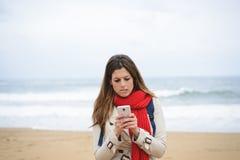 Nerwowa kobieta texting na smartphone przy plażą na jesieni Obraz Stock