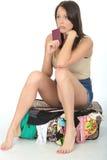 Nerwowa Niespokojna młoda kobieta Trzyma Paszportowego obsiadanie na Przelewa się walizce Zdjęcie Royalty Free