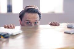 Nerwowy biznesmena zerkanie nad biurkiem zdjęcie stock