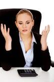 Nerwowy biznesowej kobiety obliczenie na kalkulatora beahind biurko zdjęcie royalty free
