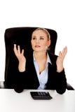 Nerwowy biznesowej kobiety obliczenie na kalkulatora beahind biurko zdjęcie stock