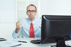 Nerwowy, dokuczający i agresywny biznesmena obsiadanie przy biurkiem w r, Zdjęcie Stock