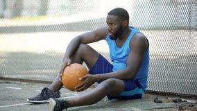 Nerwowy mężczyzna siedzi samotnego pobliskiego stadium i trzyma piłkę w sportswear, nieudacznik zdjęcia stock