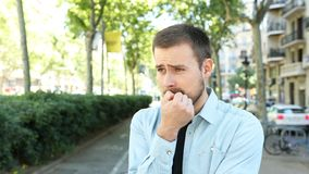 Nerwowy mężczyzny gryzienie przybija patrzeć daleko od w ulicie zbiory