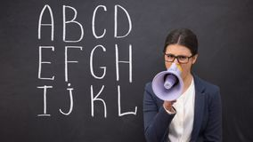 Nerwowy nauczyciel krzyczy w megafonie żąda uwagę, abecadło na blackboard zbiory