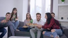 Nerwowych fan atrakcyjni młodzi ludzie oglądają dopasowanie na TV, przyjaciele przynoszą piwo i pizzę dla świętować sukces przy zbiory